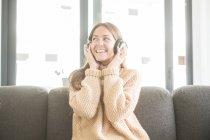 Женщина в наушниках слушает музыку сидя на диване — стоковое фото