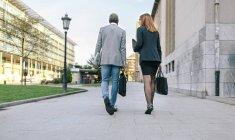 Vista posteriore di giovane uomo d'affari e donna che cammina nella città — Foto stock
