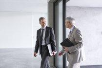 Hommes d'affaires marchant dans un immeuble de bureaux — Photo de stock