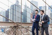США, Нью-Йорк, Бруклинский мост, два бизнесмена, гуляющие по городу с бумагами и кофейной чашкой — стоковое фото