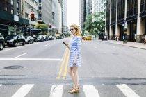 Giovane donna che cammina per strada e tiene il telefono cellulare — Foto stock
