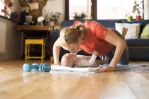 Happy mother kissing baby lying on mat next to dumbbells at home — Stock Photo