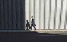 Jeune homme d'affaires marchant sur le trottoir — Photo de stock