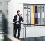Portrait of young businessman holding smartphone and tablet — Stock Photo