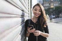 Retrato de jovem mulher asiática usando smartphone na rua — Fotografia de Stock