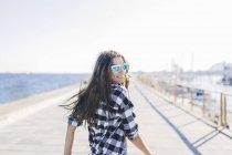 Portrait of young woman looking over shoulder on harbor — Stock Photo