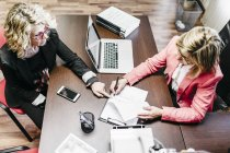 Two businesswomen working on document in office — Stock Photo