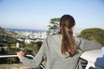 Jeune femme se penchant sur le toit de la voiture à la lumière du soleil et en regardant de vue — Photo de stock