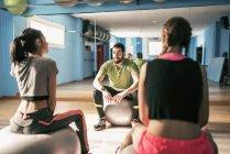 Gym coach explaining exercises to women — Stock Photo