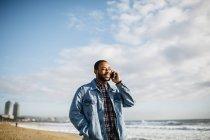 Spagna, Barcellona. Giovane viaggiatore a piedi vicino al mare, parlando con il cellulare . — Foto stock