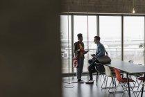 Jóvenes empresarios hablar de archivos de oficina - foto de stock