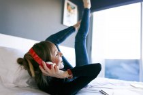 Woman lying on bed wearing headphones — Stock Photo