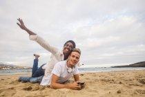 Привлекательная мультикультурная молодая пара, лежащая вместе на пляже — стоковое фото