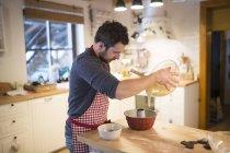 Mann stehend in Küche und Backen Guglhupf — Stockfoto
