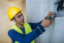 Portrait of electrician working with electrical cables of the work. — Stock Photo