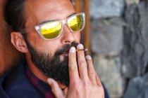 Retrato de homem usando óculos de sol espelhados fumando cigarro — Fotografia de Stock