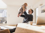 Father sitting at home and playing with baby son — Stock Photo