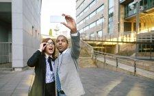 Jeune homme d'affaires et de la femme en tenant le smartphone photo — Photo de stock