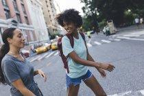 Соединенные Штаты Америки, New York City, two friends crossing the street — стоковое фото