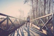 Mulher em pé na passarela de madeira com cão ao pôr do sol — Fotografia de Stock