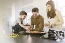 Famille préparation pizza dans cuisine ensemble — Photo de stock