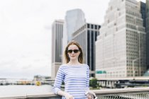 Young woman standing in Manhattan at railing, holding smartphone — Stock Photo
