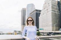 Jeune femme debout à Manhattan sur une rampe, tenant un smartphone — Photo de stock