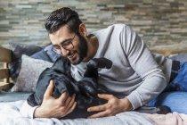 Обрезанный портрет человека, ласкающего черную собаку — стоковое фото
