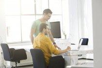 Два бизнесмена работают вместе в офисе, используя ноутбук — стоковое фото