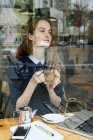 Portrait of young woman holding tea cup in cafe — Stock Photo