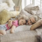 Father relaxing with sleeping daughter on sofa — Stock Photo