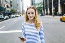 Giovane donna che cammina per strada, tenendo il telefono cellulare — Foto stock