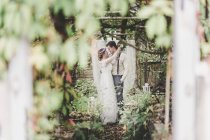 Happy bride and groom embracing in greenhouse — Stock Photo