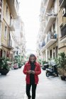 Spain, Barcelona. Portrait of young black guy in casual clothing, using mobile. — Stock Photo