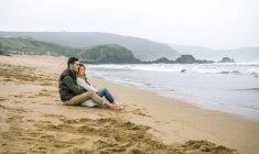 Spanien, Asturien, verliebte Paare, die sich umarmen, während sie das Meer im Sand am Strand betrachten — Stockfoto