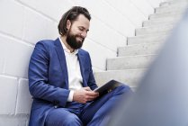 Smiling businessman using tablet on stairs — Stock Photo
