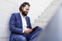 Homem de negócios usando o tablet nas escadas a sorrir — Fotografia de Stock