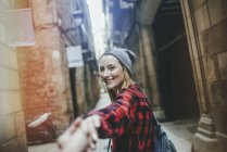 Young tourists strolling through the streets of Barcelona's Gothic quarter holding hands — Stock Photo