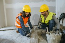 Couple of workers laying tiles at floor — Stock Photo