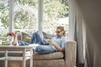 Mann entspannt sich auf Couch und nutzt Tablet — Stockfoto