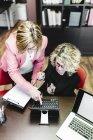 Dos mujeres de negocios usando el ordenador portátil en el escritorio en la oficina - foto de stock