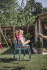 Father taking picture of daughter with cell phone in garden — Stock Photo