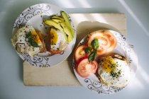 Vista superiore di uova al tegamino con fette di pomodoro e avocado — Foto stock