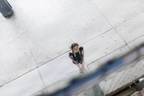 Woman with camera crossing square and looking up — Stock Photo