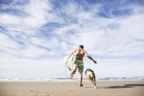 Rear view of man running with the dog holding surfboard at sandy beach — Stock Photo