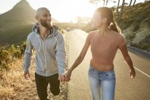 Happy young couple walking hand in hand at sunset — Stock Photo