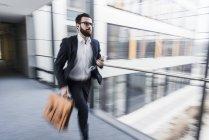 Retrato de jovem empresário correndo no corredor — Fotografia de Stock
