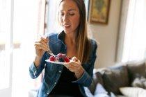 Portrait de femme manger le gâteau avec des baies à l'intérieur de rognée — Photo de stock