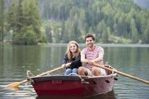 Jeune couple en bateau à rames sur le lac — Photo de stock