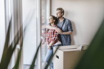 Happy couple standing at window of their new home — Stock Photo